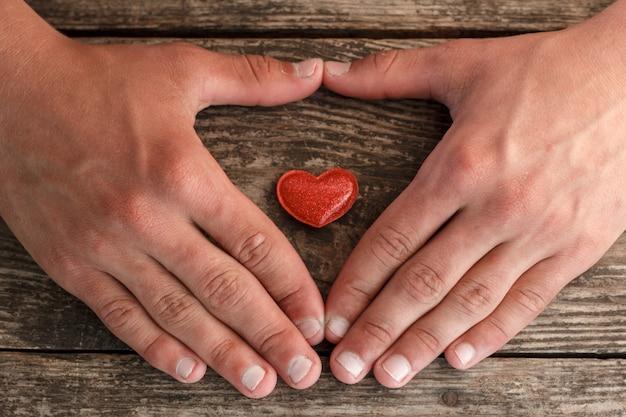 Manos y un corazón rojo que miente en un fondo de madera, concepto de salud.