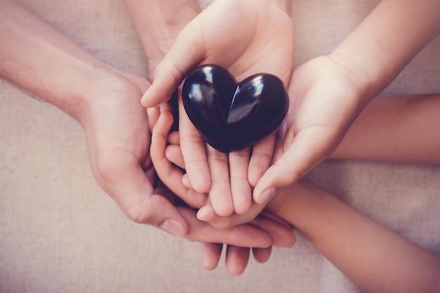 Manos y corazón rojo, seguro de salud.