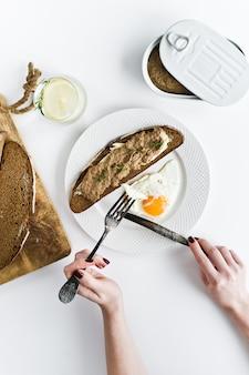 Manos cortadas con un cuchillo y un tenedor de huevo frito, paté de hígado sobre pan.