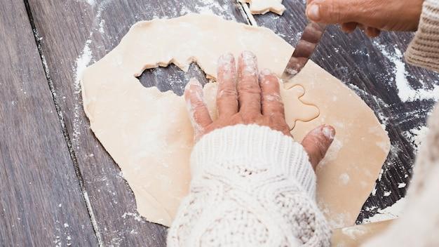 Manos cortando galletas en forma de hombre de pastelería