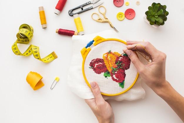 Manos cosiendo un lindo diseño de frutas sobre fondo blanco.
