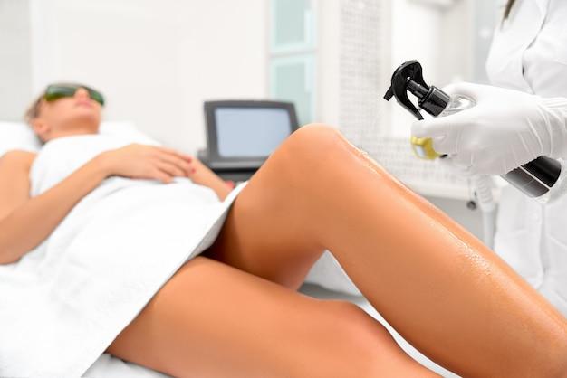 Las manos de la cosmetóloga hacen la depilación de las piernas.