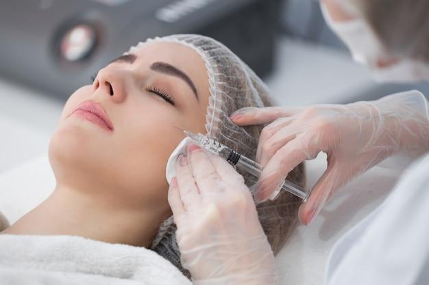Manos de cosmetóloga haciendo inyección en la cara, labios