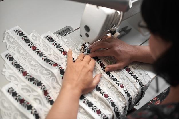 Manos de costurera cosiendo en máquina moderna