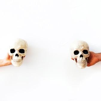 Manos con cráneos falsos
