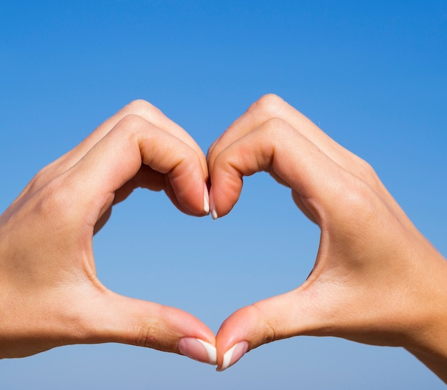 Manos creando una forma de corazón en el cielo