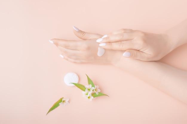 Manos con crema sobre un fondo rosa con primer plano de flores blancas. producto para el cuidado de la piel, belleza, cuidado de manos, spa.