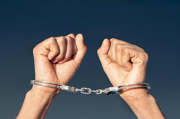 Manos criminales encerradas en esposas. vista de primer plano