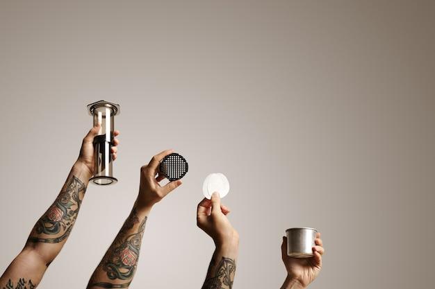 Manos de cuatro hombres con aeropress y repuestos aislados en blanco comercial de elaboración de café alternativo