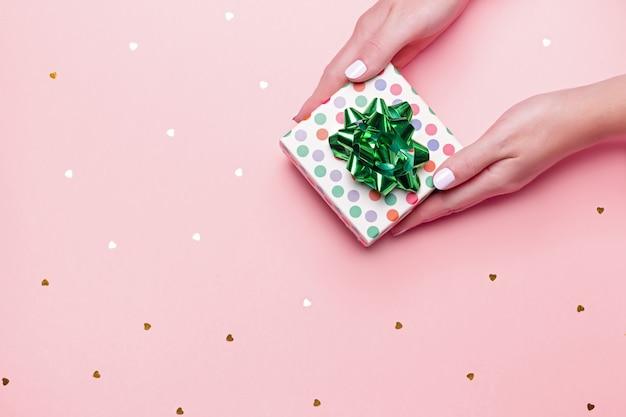 Manos cuidadas de mujer sosteniendo caja de regalo verde sobre fondo rosa pastel con confeti