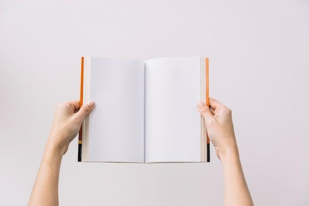 Manos de cultivo sosteniendo un libro abierto