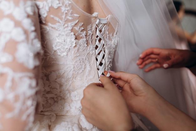 Las manos de las damas de honor están atando el corsé del vestido de novia