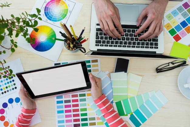 Manos de los diseñadores gráficos usan la computadora portátil y la tableta digital