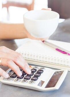 Manos de mujer sosteniendo la taza de café y la calculadora de prensa