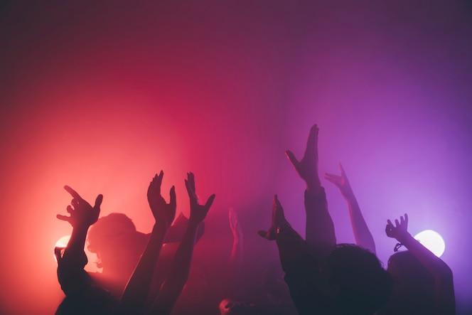 Manos de multitud en discoteca