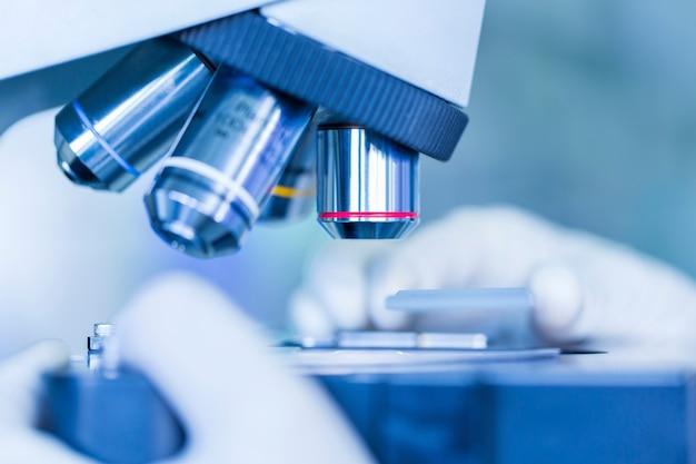 Manos del científico con microscopio, examinar muestras, ciencia conceptual y tecnología