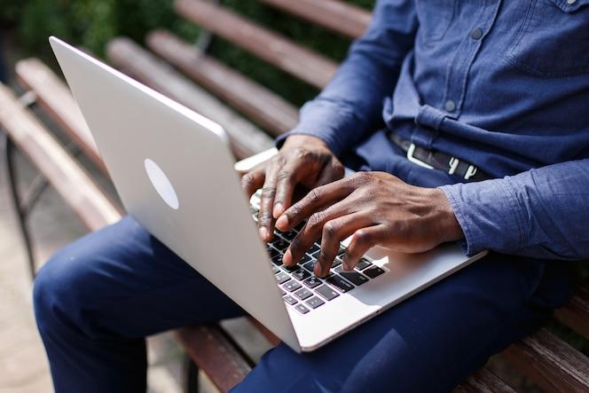 Manos del hombre afroamericano escribiendo algo en la computadora portátil mientras él se sienta en el banquillo