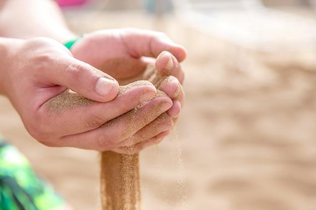 Las manos derramaron arena corriendo