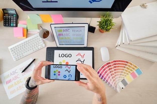 Manos del diseñador fotografiando tableta gráfica con el logotipo que dibujó en el teléfono inteligente