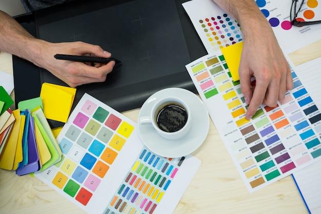 Las manos del diseñador gráfico de sexo masculino que usa la tableta gráfica