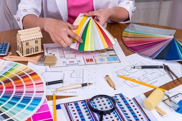 Manos del diseñador mostrando muestra colorida en el lugar de trabajo