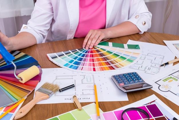 Manos de diseñador con muestra de color eligiendo color