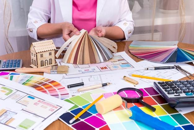 Manos de diseñadores mostrando muestreador colorido en el lugar de trabajo