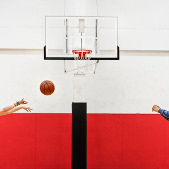 Manos disparando baloncesto al aro neto