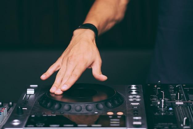 Las manos de dj controlan el primer control remoto