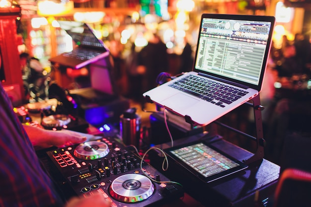 Manos de dj mezclan pistas en un tocadiscos digital y software en una computadora portátil con software de mezcla profesional