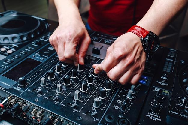 Manos dj mezclando música en el club durante el evento