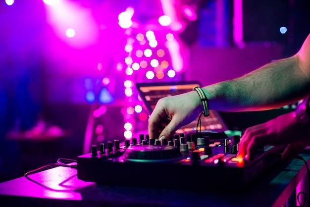 Manos dj mezclando y tocando música en un mezclador controlador profesional