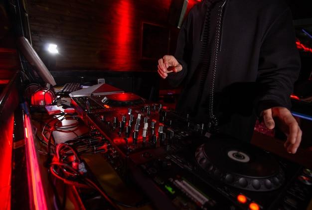 Manos de dj en la plataforma del equipo y el mezclador en la fiesta. disparo de disc jockey con capucha negra mezclando música en un club nocturno. concepto de vida nocturna. salir con los amigos.