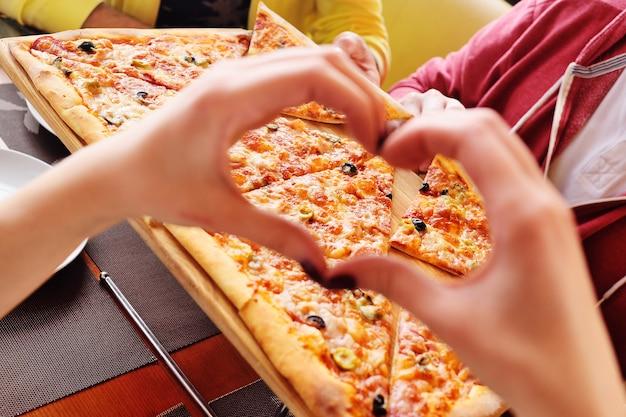 Manos dobladas en la forma de un primer plano del corazón en el fondo de pizza caliente fresca
