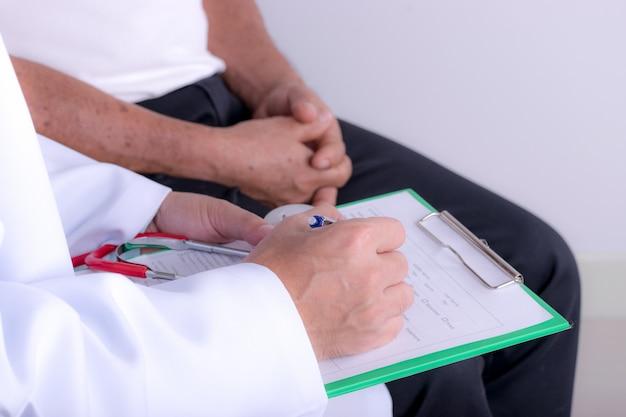 Manos del doctor con la carta de cardiograma con pluma. cardiólogo explicando los resultados del ekg de su paciente.