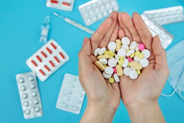 Las manos del doctor sostienen píldoras. cura para el coronavirus. remedios médicos en la lucha contra covid-19. píldoras, jeringas, termómetro, máscara médica en mesa azul.