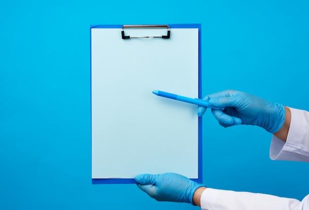 Las manos de la doctora en guantes de látex médicos azules sostiene una carpeta con un clip y un bolígrafo de plástico