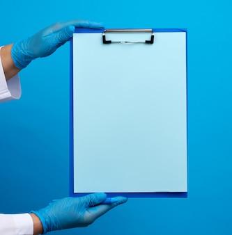 Las manos de la doctora en guantes médicos azules de látex tiene una carpeta con un clip