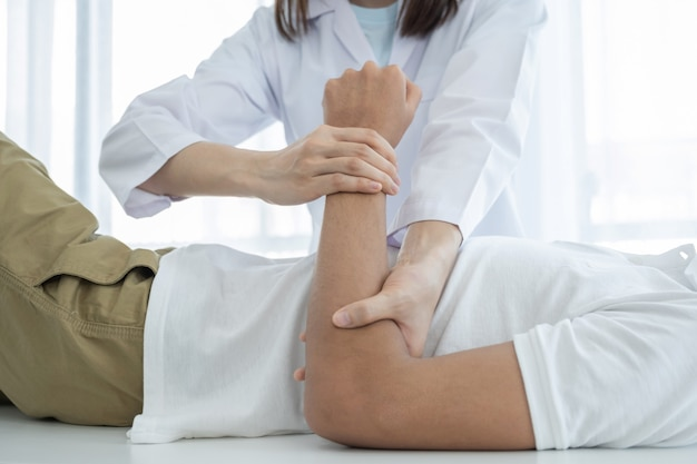 Manos de la doctora haciendo fisioterapia extendiendo el brazo de un paciente masculino.