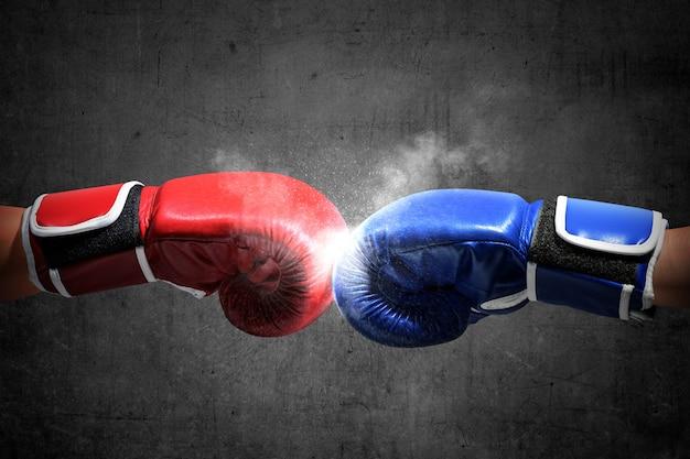 Las manos de dos hombres con guantes de boxeo azules y rojos golpearon sus puños