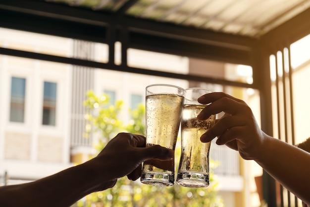 Las manos de dos hombres que sostienen un vaso de cerveza se levantaron para beber para celebrar el éxito.