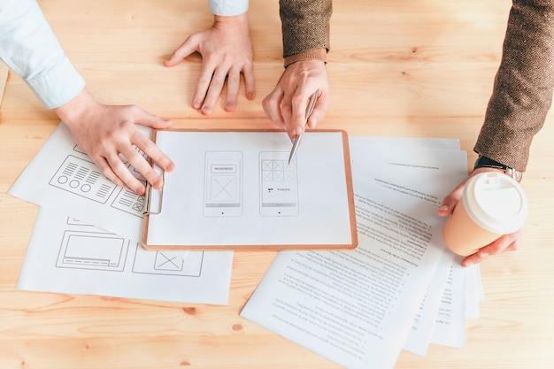 Manos de dos jóvenes diseñadores web o programadores discutiendo uno de los documentos con la aplicación de software en la reunión de trabajo