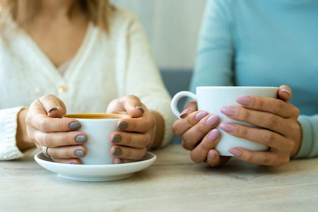 Manos de dos mujeres jóvenes amistosas en ropa casual sosteniendo tazas con café mientras está sentado en la mesa de café