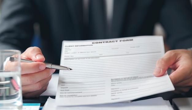 Manos ejecutivas sosteniendo una pluma y un formulario de contrato, indicando dónde firmar.