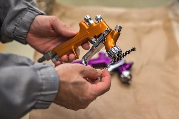 Las manos de un empleado del taller de pintura y limpieza de la pistola rociadora