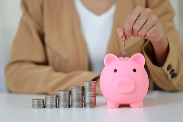 Manos de empresaria asiática inteligentes y activas poniendo monedas en la alcancía con crecimiento de ahorro en apilar monedas en la mesa