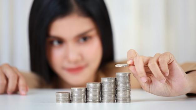 Manos de empresaria asiática inteligentes y activas poniendo monedas en apilar monedas que crecen en el cuadro blanco y fondo blanco.