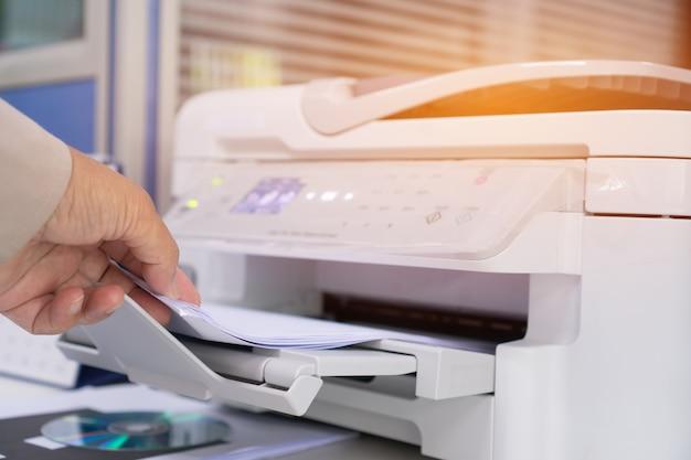 Manos de la empresaria que trabajan en el proceso de prensa de papel en impresora láser en el escritorio de trabajo ocupado