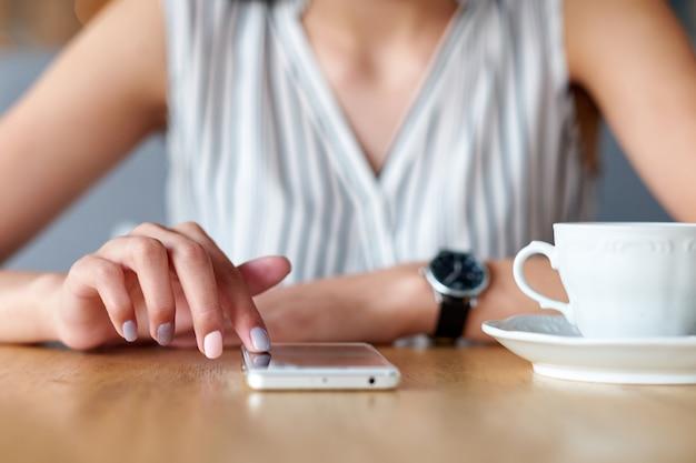 Manos de la empresaria con teléfono y taza de café.