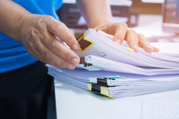 Manos de la empresaria trabajando en archivos de papel de stacks para buscar y verificar documentos